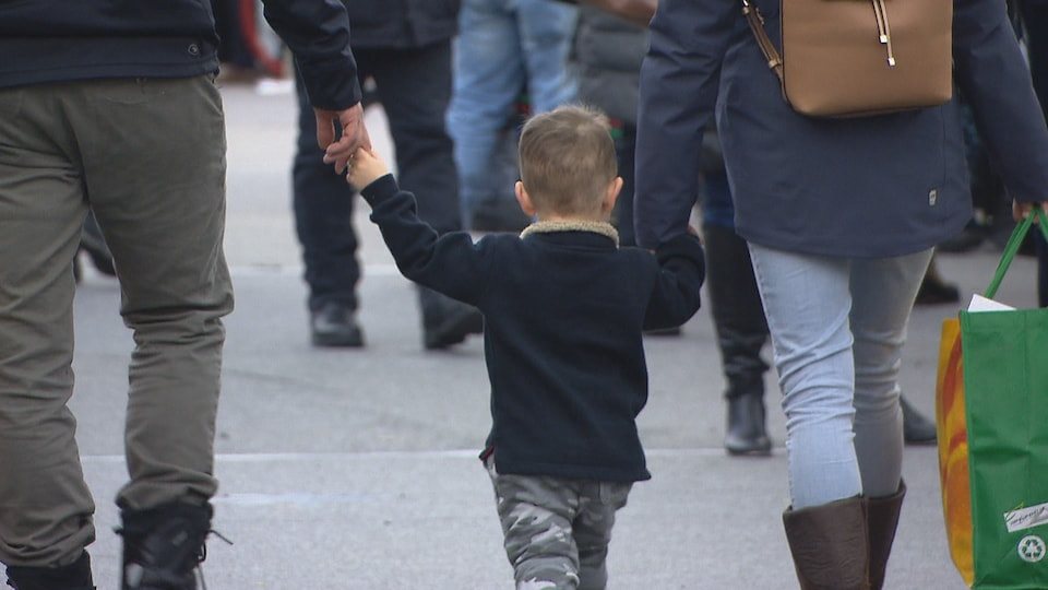 Un bambin tient la main de ses parents.