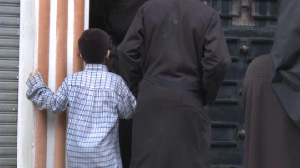 Un petit garçon et des membres de Lev Tahor, devant une porte au Guatemala.