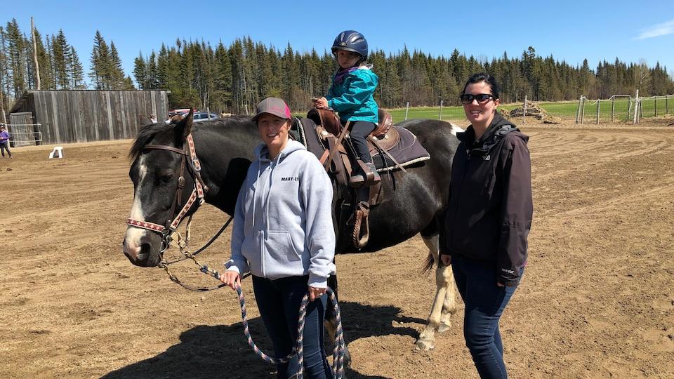 Une fillette à cheval accompagnée de maman et d'une instructrice