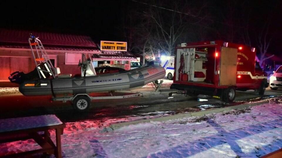 Un camion et un bateau des autorités la nuit dans la neige.