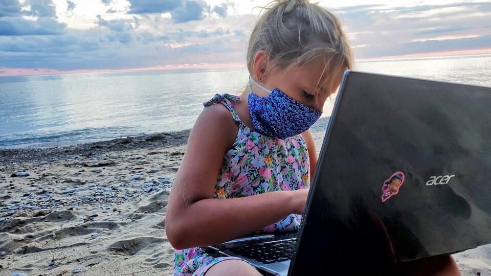 Une enfant sur la plage avec un ordinateur portable.