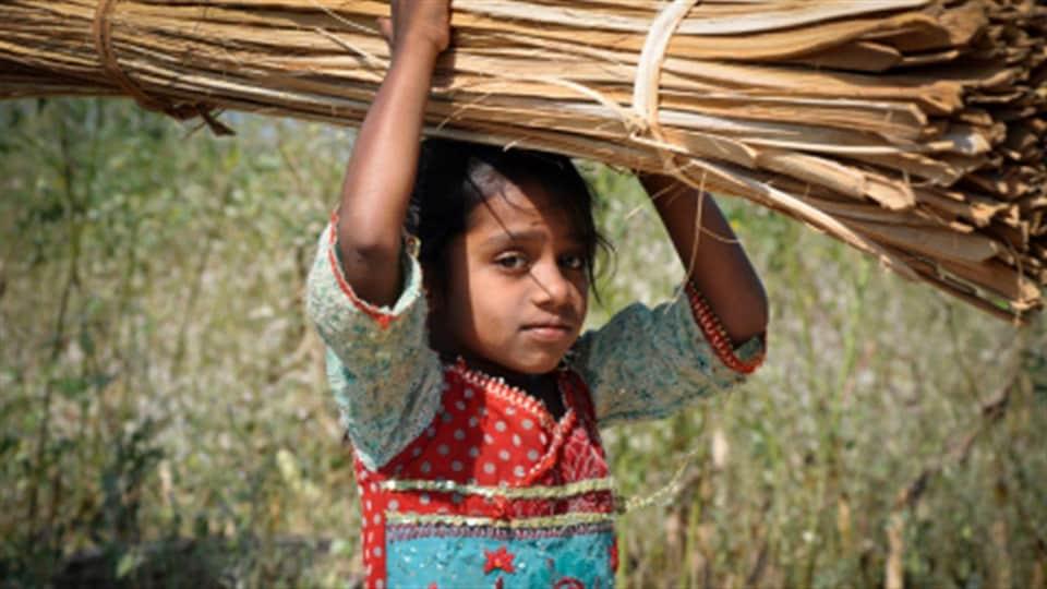 Enfant portant des branches sur sa tête.