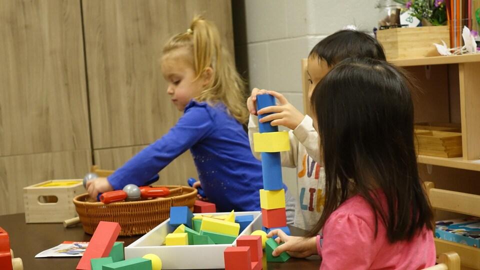 Trois enfants jouent avec des blocs.
