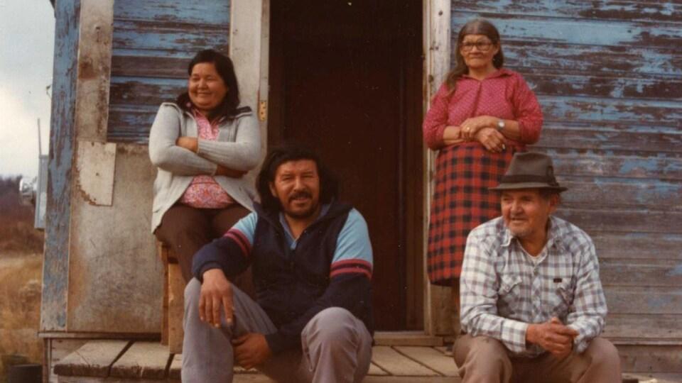 Photo de quatre personnes assises sur le perron d'une maison en bois.