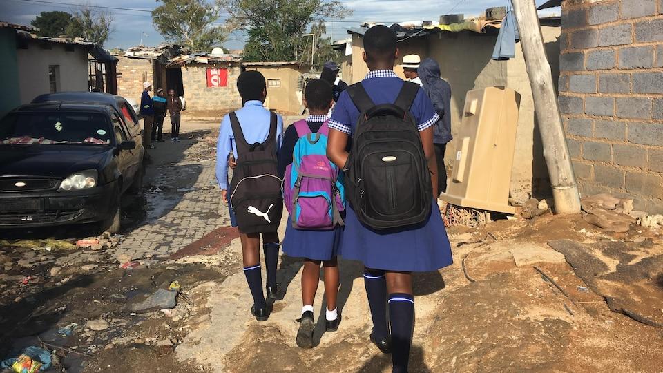 Des enfants en uniforme et avec un sac à dos marchent dans la rue.