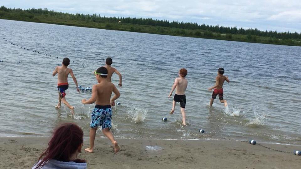 Des jeunes courent dans l'eau d'un lac.