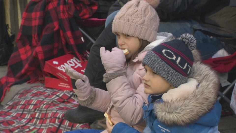 Deux enfants habillés chaudement regardent le défilé en mangeant des biscuits.