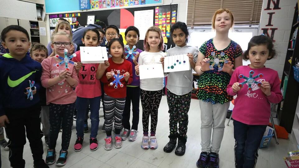 Quatre enfants tiennent dans leurs mains des cartes de Noël et des flocons de neige fabriqué en bois.