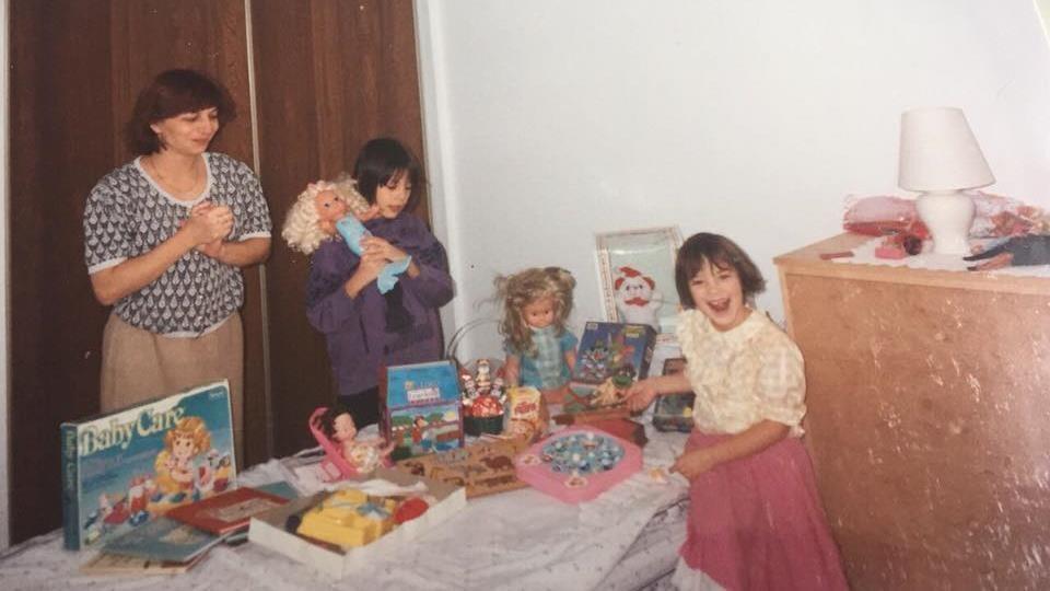 Une mère et ses deux enfants heureux devant leurs cadeaux de Noël.