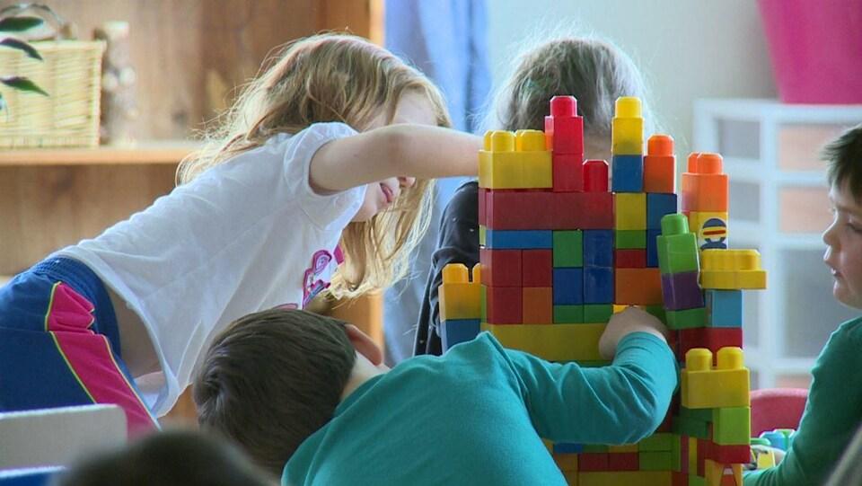 Des enfants jouent avec des blocs colorés.