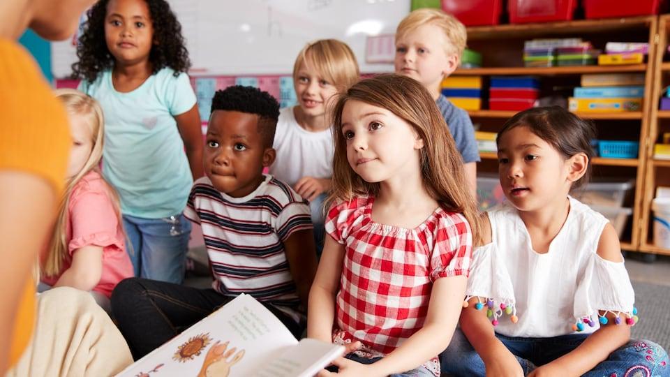 De jeunes enfants écoutent une personne qui a un livre dans la main.