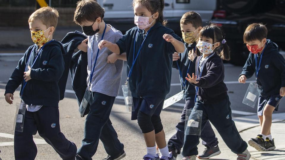 Des enfants qui portent le masque traversent la rue à Vancouver.