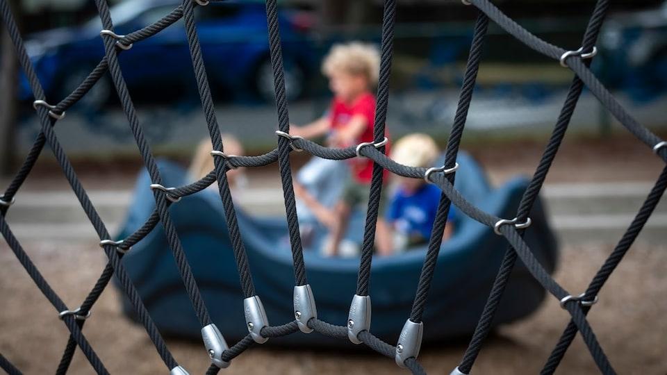 Trois enfants jouent au parc.