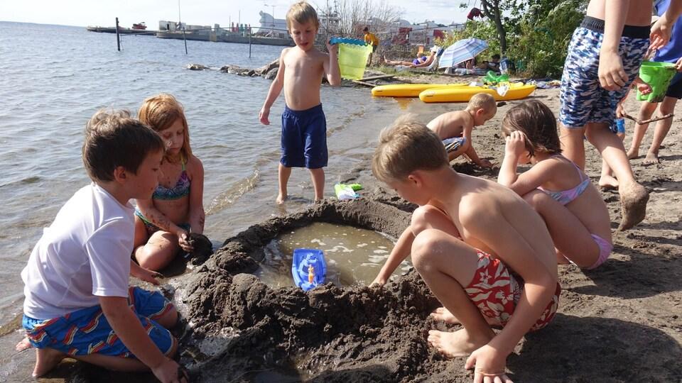 Des enfants jouent dans le sable à la plage.