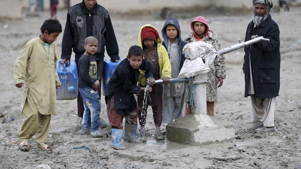 Des enfants qui s'abreuvent de l'eau publique grâce à une pompe à l'extérieur de Kaboul.