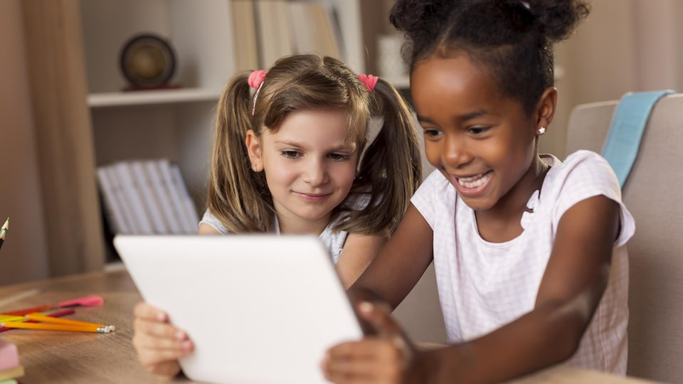 Deux jeunes filles regardent une tablette.