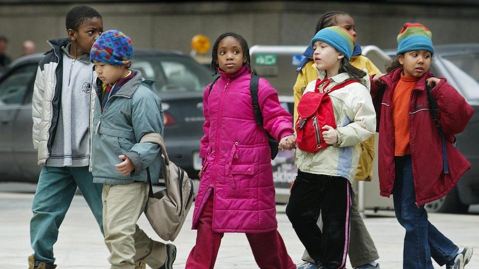 Six enfants avec leur sac à dos marchent sur le trottoir, devant des voitures.