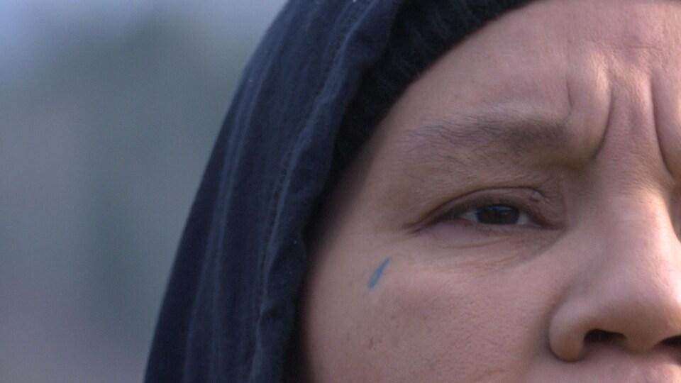 Gros plan sur le visage de Ceejai Julian. Elle a un tatouage en forme de larme sous l'oeil droit.
