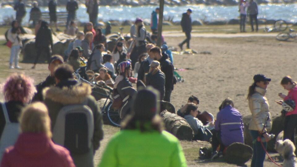 La plage d'English Bay est remplie de gens, dont certains sont rassemblés en groupe.