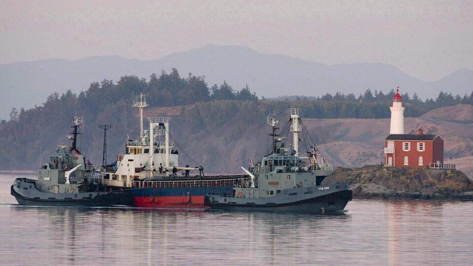 Deux bateaux escortent un autre plus gros navire près d'un phare.