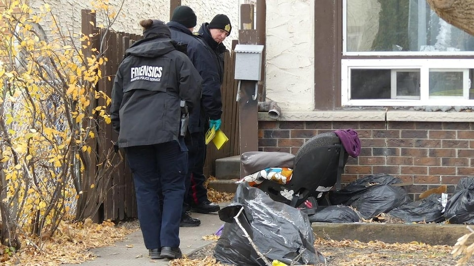 Des policiers sont à l'extérieur d'une maison.