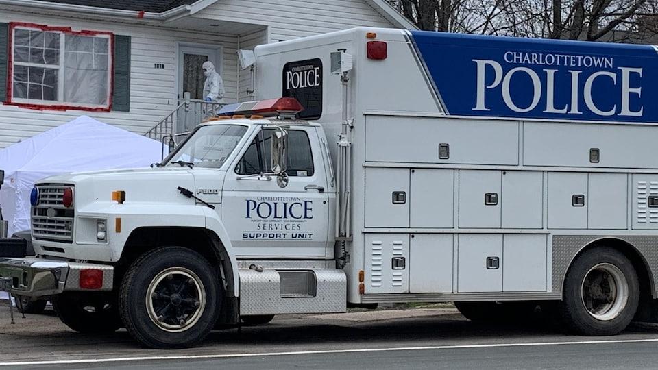 Un camion de police devant une résidence et une personne en combinaison Hazmat sur le perron.