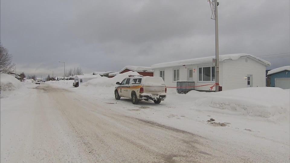 Un véhicule de la Sûreté du Québec est stationné devant une maison.