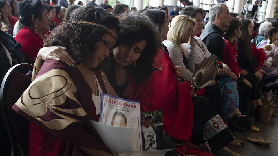 Deux femmes se serrent assises sur leur chaise en écoutant les discours prononcés lors de la cérémonie de clôture de l'enquête.