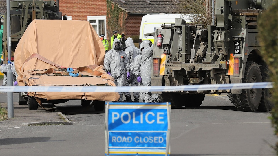 Des militaires portant des tenues de protection circulent entre un véhicule militaire et un véhicule qui va être transporté.