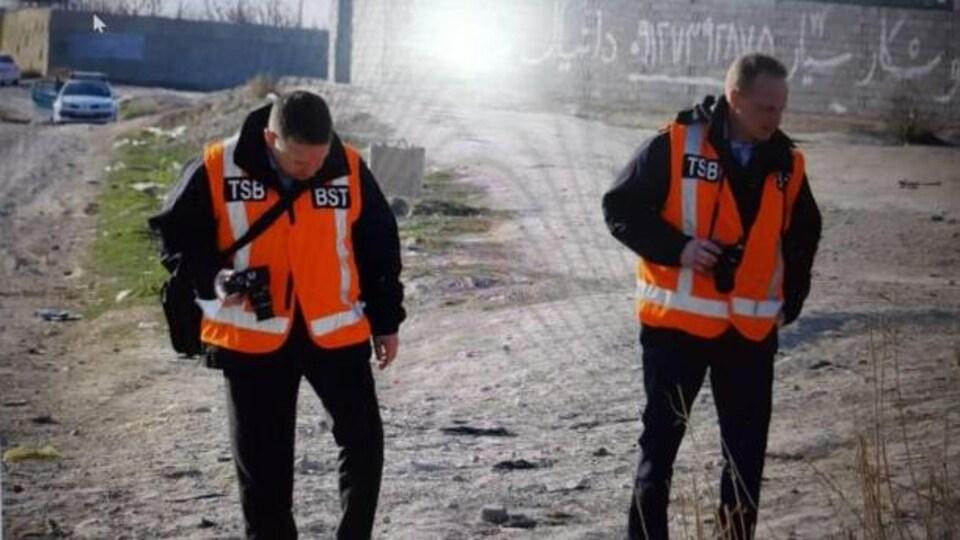 Deux hommes portant des vestes oranges sur lesquelles on peut voir les lettres TSB et BST marchent sur un site extérieur, appareil photo en main.