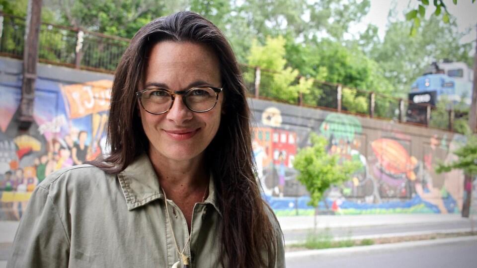 Une femme sourit et porte des lunettes. Derrière elle se trouve une murale colorée.
