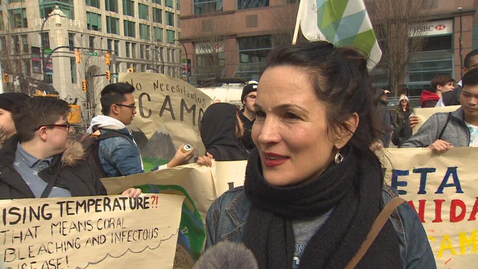 Une femme avec des pancartes dans l'arrière-plan.