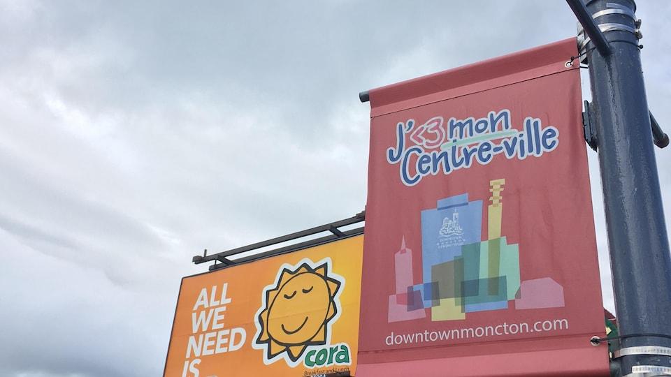 Un panneau publicitaire de Cora jouxte une affiche qui vante le centre-ville de Moncton.