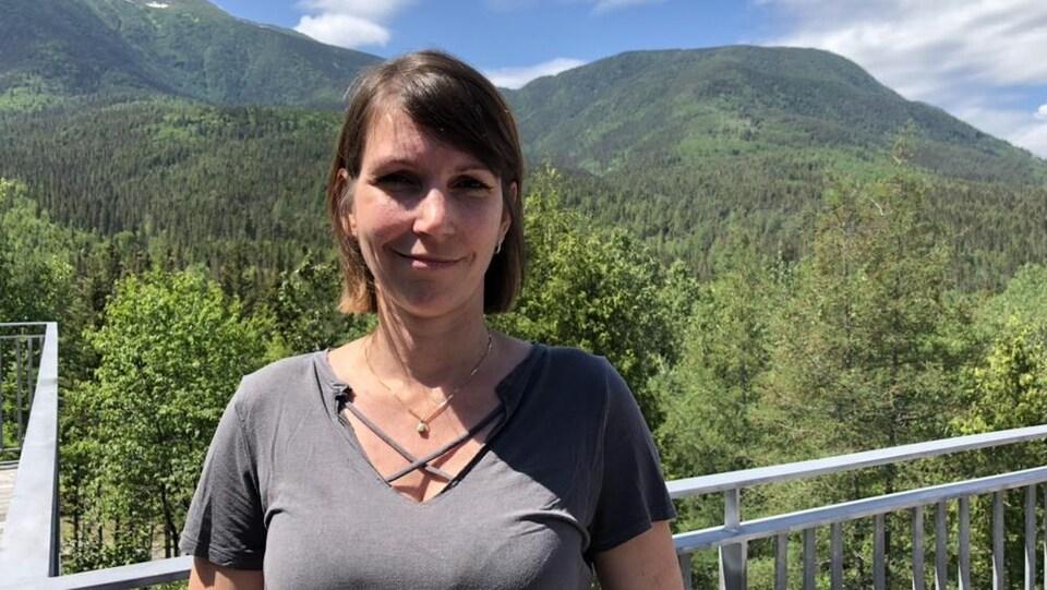 Elle est souriante avec la montagne derrière elle.
