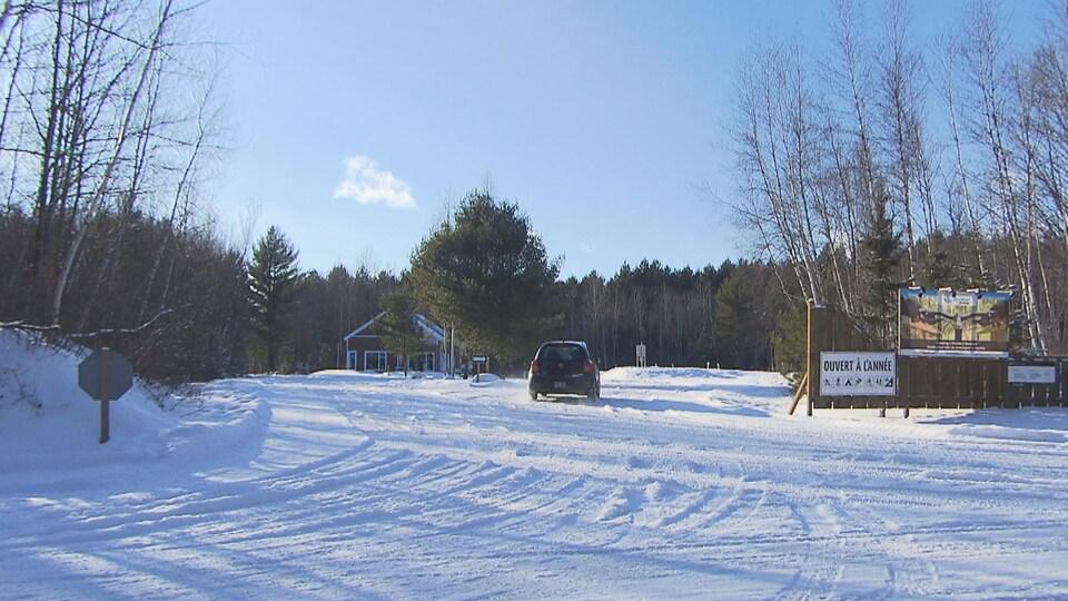 Une cabane au loin, avec une voiture qui entre dans l'espace boisé.