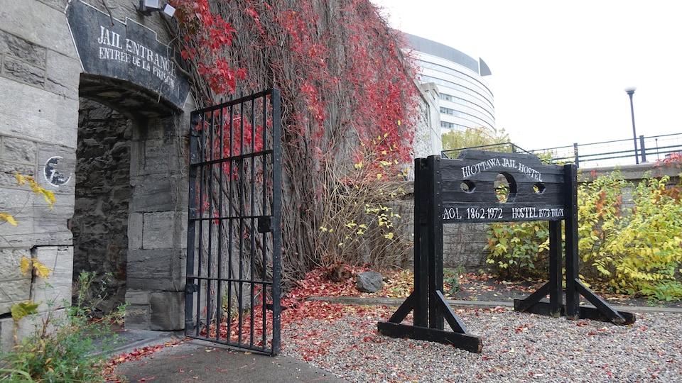 Une porte de fer est ouverte sur un mur de pierre couvert des branches grimpantes d'un arbre en automne.