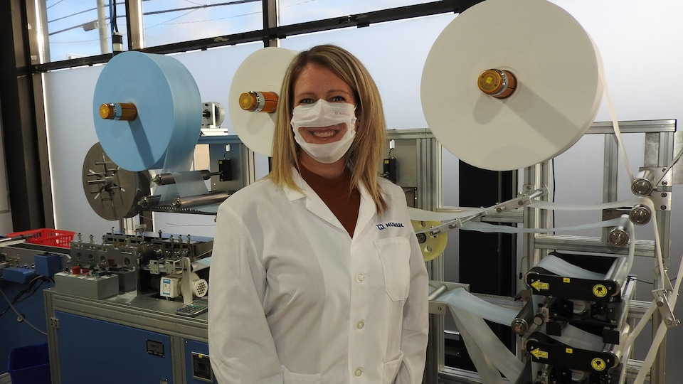 Une femme avec un masque transparent dans une usine.
