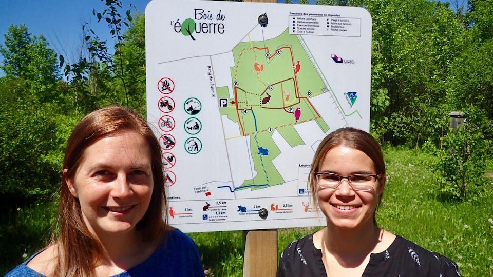 Virginie Dufour, responsable des dossiers de l'environnement au comité exécutif de la vile de Laval, et Louise Morin, consultante pour l'équipe Milieux naturels du Service de l'environnement de Laval. Elles posent devant une affiche qui indique les sentiers du Bois de l'Équerre