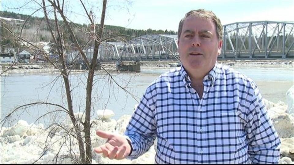L'homme en entrevue à l'extérieur, devant un pont.