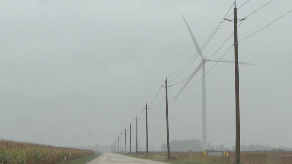 Une route à travers champs avec une énorme éolienne à droite