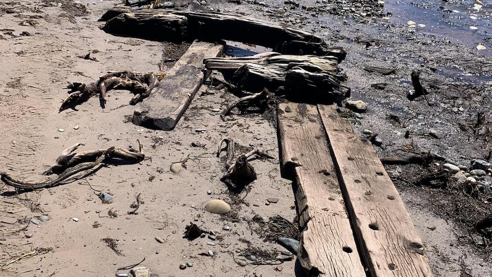 Planches de bois très vieilles échouées sur la plage.