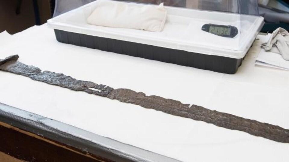 Une vieille épée, dont le métal est oxydé.