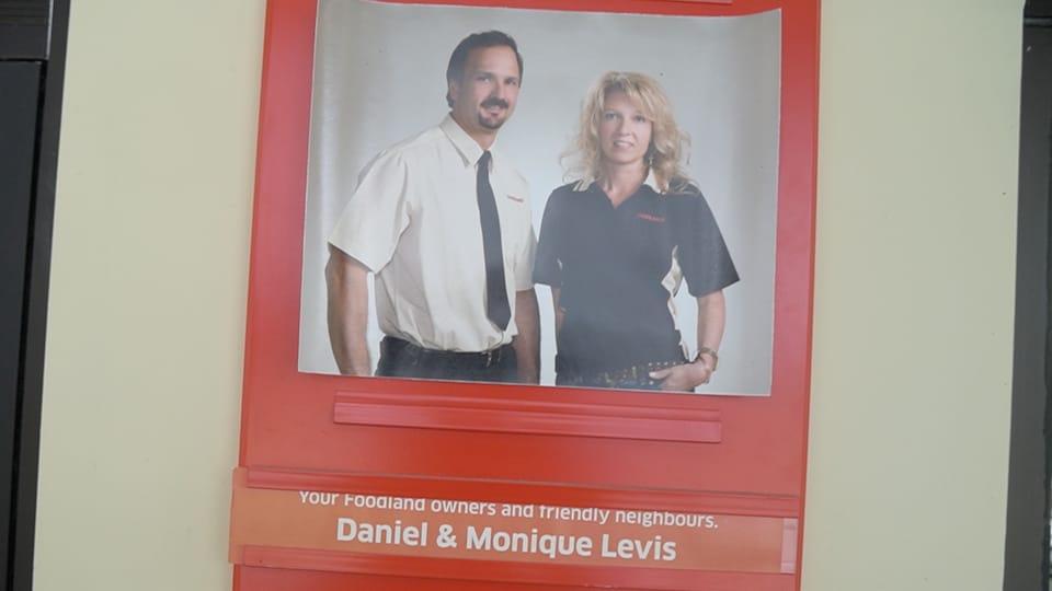 Monique et Daniel posent sur l'affiche à l'entrée du magasin.