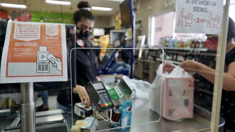 Derrière un plexiglas, une caissière présente le terminal de paiement à un client.