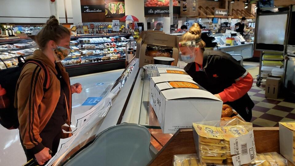 Une cliente devant un comptoir d'alimentation, derrière lequel une employée la sert.