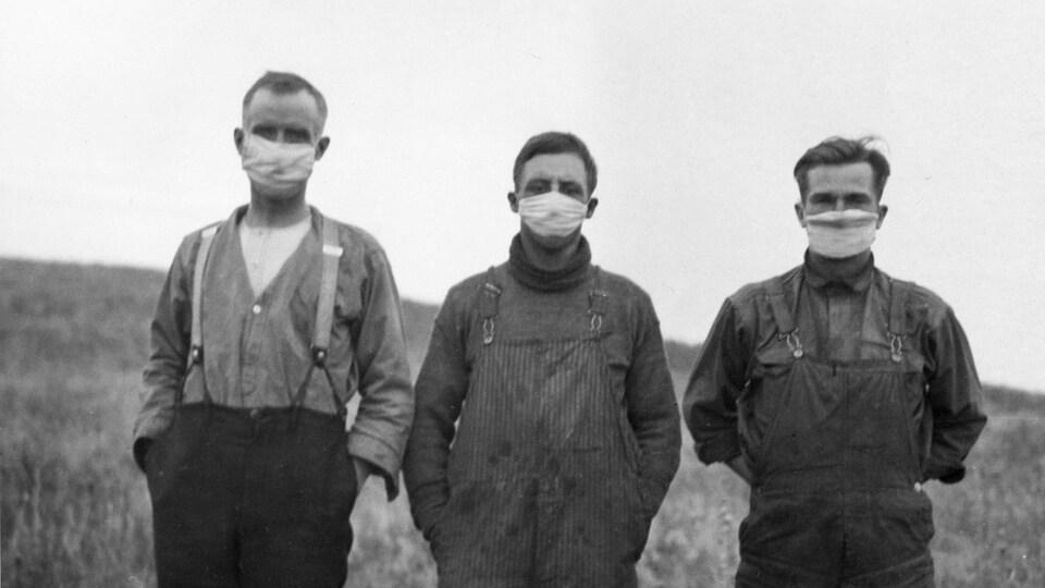 Photographie d'archive en noir et blanc montrant trois hommes arborant un masque anti-projection. Les hommes se tiennent côte à côte. Derrière eux, on aperçoit un champ.