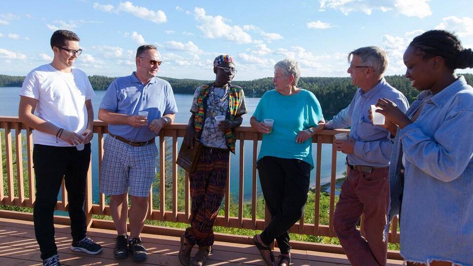 Les six personnes sur un balcon face au lac, un verre à la main