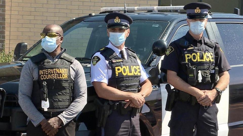 Deux policiers et un intervenant posent devant une voiture de la Police provinciale de l'Ontario .