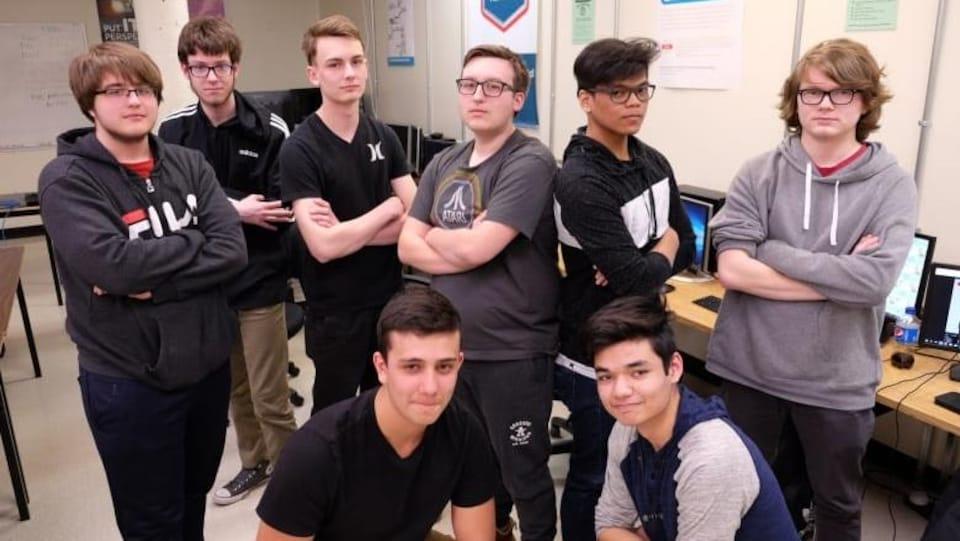 Huit jeunes élèves posent devant la caméra dans une salle de classe.