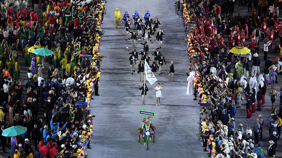 Ils sont derrière le drapeau olympique.